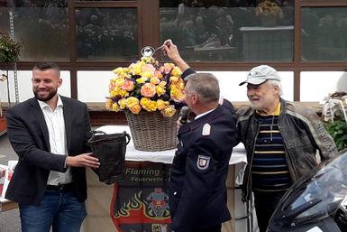 Landesbrandmeister Frank Homrich, tauft die Rose auf den Namen Flaming Star®. Unterstützt wird er dabei von Wilhelm-Alexander Kordes und Jasper Vogt.